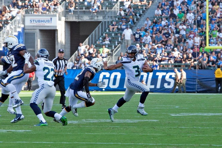 Seahawks quarterback Russell Wilson appears to stiff a Chargers defender in preseason action. Photo by Astrud Reed/News4usonline