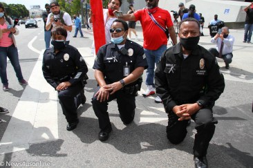 Three Black LAPD police officers take a knee in solidarity with demonstrators out in downtown Los Angeles, California, protesting the killing of George Floyd, on June 2, 2020. The march was led by the Baptist Ministers Conference. to protest police brutality and show solidarity behind a Black Lives Matter movement to hold police and law enforcement agencies more accountable. Demonstrators came out to also protest the death of George Floyd, a 46-year-old Minneapolis man who died in police custody on May 25, 2020. Photo credit: Dennis J. Freeman/News4usonline