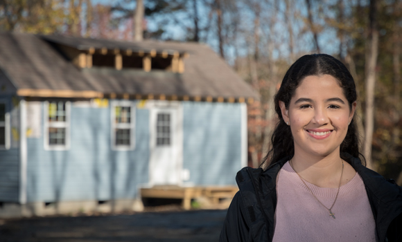 Portrait of Ocasio in front of the tiny house she designed.