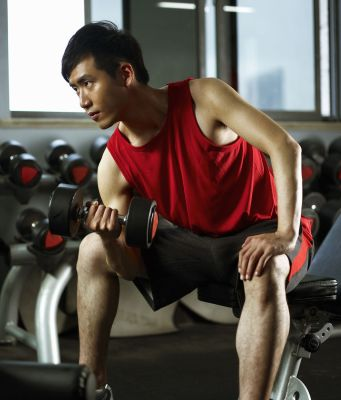 man sitting on weight bench lifting dumb bells royalty free image 1134418332 1557166788