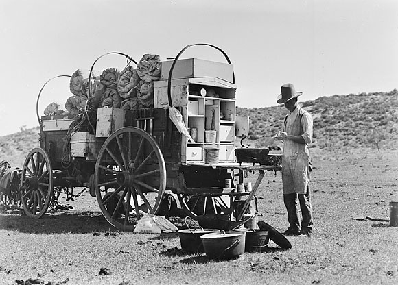 cook standing next to chuck wagon