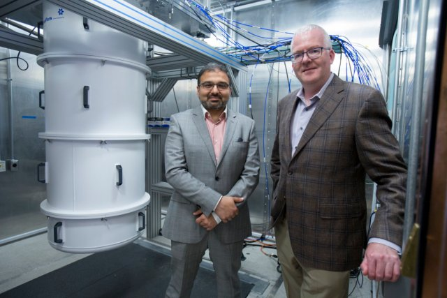 Photo - Irfan Siddiqi (left), director of the Lab's AQT effort, and Jonathan Carter, AQT co-principal investigator, in front of a dilution refrigerator housing superconducting qubits. Siddiqi is a staff scientist in Berkeley Lab's Material Sciences Division and Carter is the deputy of science for Berkeley Lab's Computing Sciences Area. (Credit: Peter DaSilva, Berkeley Lab)