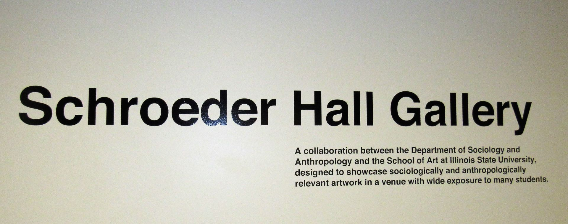 Text: The Schroeder Hall Gallery is a collaboration between the Department of Sociology and Anthropology and the Wonsook Kim College of Fine Arts at Illinois State University and is designed to showcase sociologically and anthropologically relevant artwork in a venue with wide exposure to students.