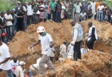 The photo taken on October 20, 2014 in the town of Beni, in the eastern Democratic Republic of the Congo, shows people attending the burial of victims of a massacre by ADF-NALU
