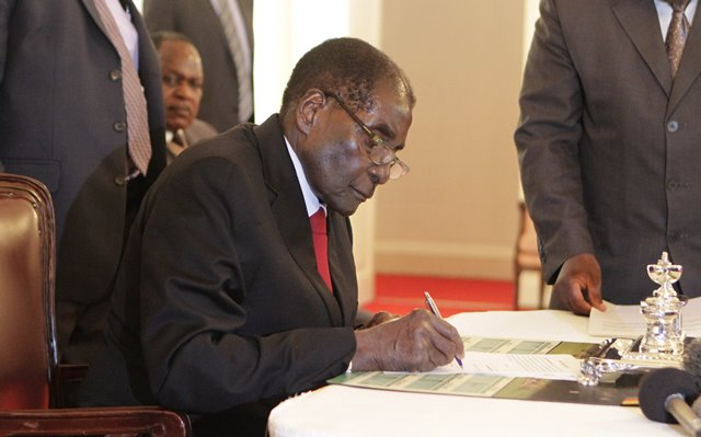 Zimbabwean President Robert Mugabe signs the documents to swear in new ministers at State House in Harare, Zimbabwe, on July 6, 2015. The Zimbabwean veteran leader on Monday reshuffled his cabinet for the second time in barely six months. (Xinhua/Stringer)