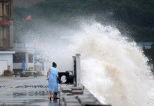 A resident is hit by splashing water from a bank at a scenic spot in Zhoushan City of east China's Zhejiang Province, July 10, 2015 . Typhoon Chan-Hom is expected to land somewhere between Sanmen and Zhoushan in east China's Zhejiang Province on Saturday afternoon, the National Meteorological Center (NMC) forecast. (Xinhua/Wu Linhong) (zwx)