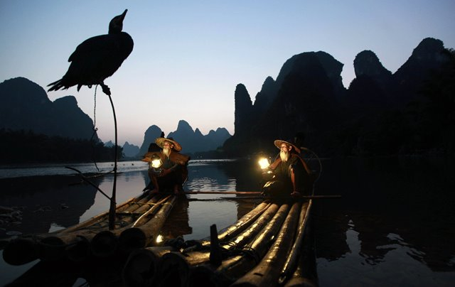 Two brothers in their 70s and 80s, working as photographer's models, take a break on a bamboo raft in Lijiang River of Guilin, south China's Guangxi Province, July 15, 2015. (Xinhua/Liu Jiaoqing)