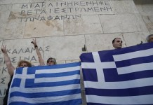 Men hold Greek flags in front of the Greek parliament during an anti-austerity rally in Athens, Greece, on July 13, 2015. (Xinhua/Marios Lolos)