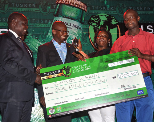 Minister of State for Finance Fred Omach (L) and UBL Managing Director Nyimpini Mabunda (2nd left) present a trophy and a cheque to Eva Magala and professional golfer David Wakhu after the Pro-Am tournament at Kitante. Photo by Michael Nsubuga