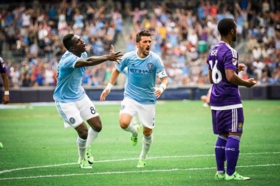 Poku leads David Villa to celebrate