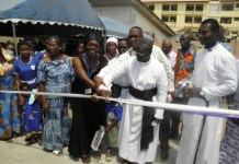 MP being assisted by Rev. Benjamin Robertson, Anglican Priest of St. Augustine Church, Dansoman, to cut the tape for the inauguration