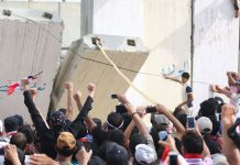 Iraqi protesters open a breach in a concrete wall surrounding the parliament on April 30, 2016 (AFP Photo/Haidar Mohammed Ali)