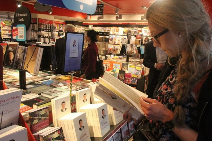 People stop by Chinese-themed books, such as Xi Jinping: Governance of China and the Analects of Confucius in a bookstore at Warsaw Chopin Airport. (Photo: Wang Yunsong from People's Daily)