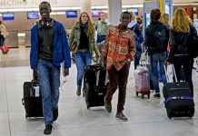 Thomas Nellon, left, 17, and his brother Johnson Nellon, 14, of Liberia, smile at their mother in the arrivals area at John F. Kennedy International Airport in New York earlier this month. The brothers received a health screening upon arrival. The U.S. says it will step up screening measures for arrivals from Ebola-affected West African countries.