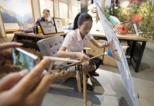 A folk artist demonstrates the technique of making oil-paper umbrella at an exhibition hall of traditional arts and crafts in the Qiaoxi historic block near the Gongchen Bridge in Hangzhou, capital city of east China's Zhejiang Province, Sept. 1, 2016. Traditional handicrafts and local intangible cultural heritages were demonstrated there. (Xinhua)