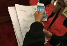 A journalist is canning the QR code to check the content of the government work report. (Photo by gov.cn)