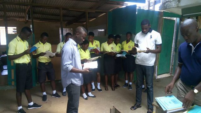 A cross-section of teachers and students of Apex College going through some of the books