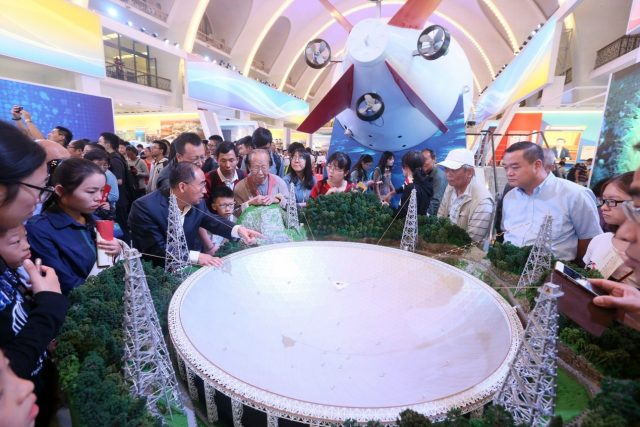 """Visitors get an introduction to China's 500-meter Aperture Spherical Radio Telescope (FAST), nicknamed """"Tianyan"""", at the exhibition of China's progress over the past five years in Beijing, Oct. 1, 2017. (Photo by People's Daily Online)"""