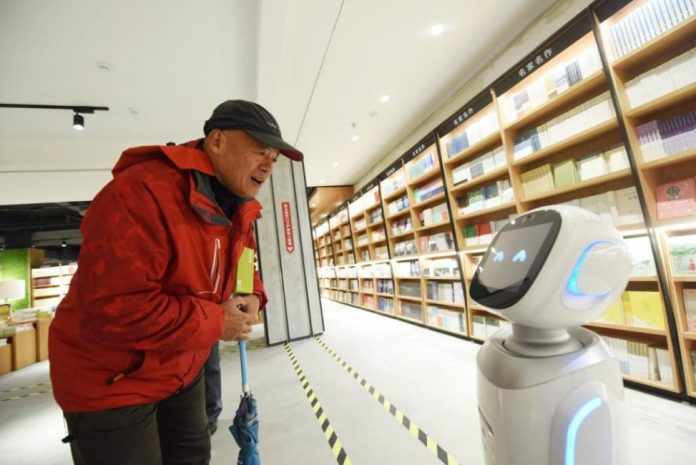 A visitor interacts with an AI robot at a bookstore in Hangzhou, East China's Zhejiang Province on December 15. (Photo: CFP)