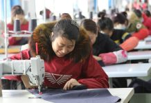Left-behind women and poor migrant workers make down jackets ordered by customers at a poverty alleviation workshop in an industrial concentration area in Guangshan County, central China's Henan province, March 9, 2018. (Photo from CFP)
