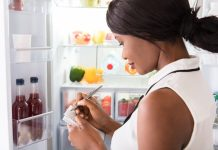 Close-up Of Young African Woman Writing On Spiral Book Near Open Refrigerator