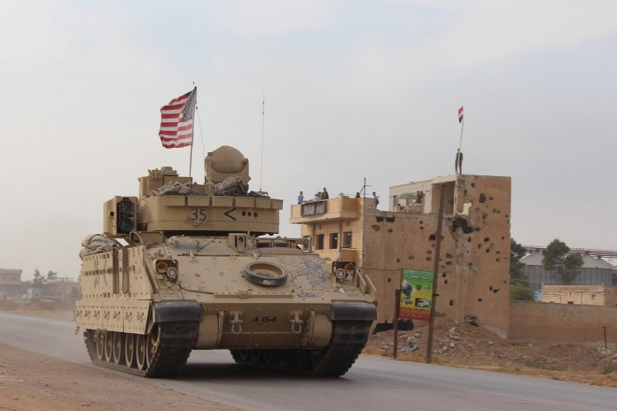 A U.S. military vehicle runs past the Tal Tamr area in the countryside of Hasakah province, northeastern Syria, on Nov. 14, 2019. (Str/Xinhua)