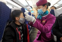A train attendant takes body temperature of a boy on train D354 from Chengdu East Railway Station to Shanghai Hongqiao Railway Station, Feb.2, 2020. A travel rush is seen after the Spring Festival holiday. To contain the spreading of the novel coronavirus, the train attendants have to inspect train cabins on a regular basis, and observe passengers and ask if they have such symptoms as fever, cough and dyspnea, so as to ensure safe travels. By Hu Zhiqiang, People's Daily Online