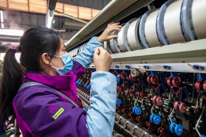 A woman works at a silk reeling workshop of Guangxi Jingxi Xinsheng Cocoon Silk Technology Co., Ltd. in Jingxi county, Guangxi Zhuang Autonomous Region, March 3, 2020. Zhao Jingwu/People's Daily Online
