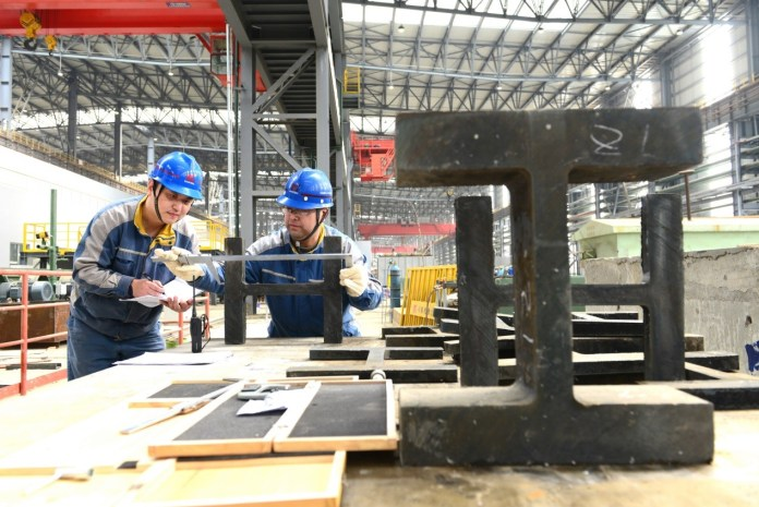 Workers examine an H-shaped steel product at a factory of Masteel Group, east China's Anhui province, April 3. Photo by Zhang Lei, www.cpanet.cn
