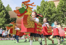 """Children compete ina cardboard """"dragon boat race"""" at a kindergarten in Tengzhou, east China's Shandong province, June 24. Photo by Song Haicun/People's Daily Online"""