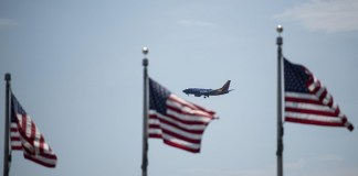 """A plane flies in the sky with the U.S. national flags in the foreground in Washington, D.C., the United States, on July 21, 2020. U.S. President Donald Trump said Tuesday afternoon that the coronavirus pandemic in the United States will probably """"get worse before it gets better."""" More than 3.8 million people in the United States have infected with the virus, with more than 141,000 deaths, according to a count by Johns Hopkins University, as some states, including Florida, are seeing a surge in cases. (Xinhua/Liu Jie)"""