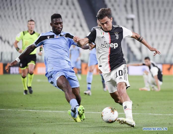FC Juventus' Paulo Dybala (R) vies with Lazio's Bastos during the Serie A football match in Turin, Italy, July 20, 2020. (Photo by Federico Tardito/Xinhua)