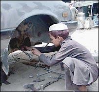 Boy repairs axle in Peshawar, Pakistan