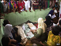 Residents gather around the victims of a flood in Bohorok, North Sumatra