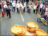 A contestant tries to knock Yorkshire puddings off a ledge by throwing a black pudding in Ramsbottom - (c) MEN Syndication