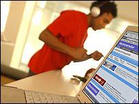 Man wearing headphones next to a computer
