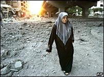 A Lebanese woman walks through rubble from an Israeli air raid in Beirut