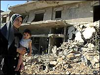 Mother and child outside ruined building