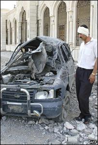Iraqui herido observa un vehículo usado como carro bomba