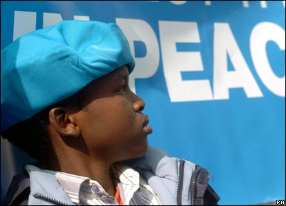 A Darfurian boy sporting a UN peacekeeper-style blue beret outside the Sudanese embassy in London.