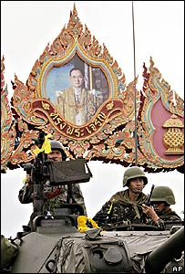 Thai soldiers man a tank under an archway featuring a portrait of revered King Bhumibol Adulyadej