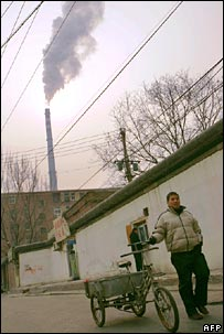 Man pushing bike in front of Beijing power station. Image: AFP/Getty