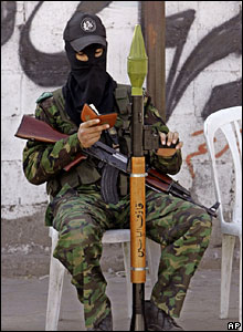 A Hamas militant reads from the Koran as the funeral of a bodyguard of Prime Minister Ismail Haniya takes place
