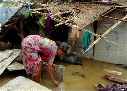 An Indian woman attempts to remove flood water from her home in Kolluru.