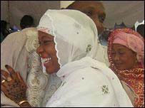 A wedding couple laugh and hug