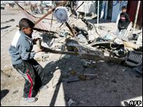 Boy inspecting bomb damage last month