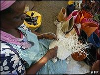 A Kenyan woman handweaves baskets