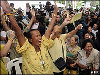 Workers and supporters of Thailand's Democrat Party celebrate  the court's decision in their favour at the party's headquarters in Bangkok, 30 May 2007.