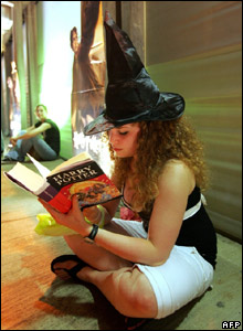 A woman in a witch's hat reading a Harry Potter book in Tel Aviv