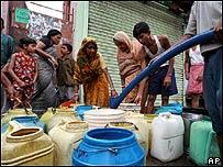 Habitantes de Calcuta, en India, llenan bidones con agua